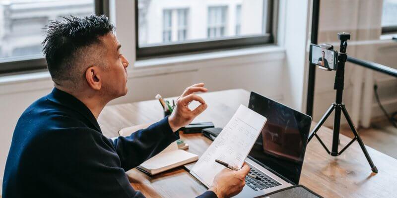 Imagem de um homem em frente um computador e um celular gravando um vídeo. imagem ilustrativa texto franquia de educação qualifica cursos.