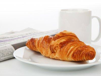 Foto de um croissant ao lado de uma xícara de café e jornal. Imagem ilustrativa para texto franquia de fast-food croasonho.