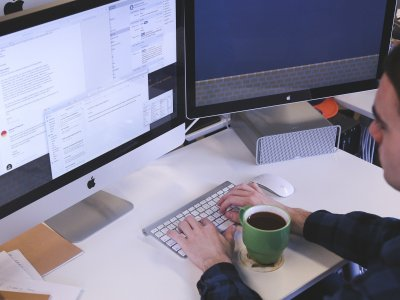 Foto de um homem usando o computador com uma caneca ao lado. Imagem ilustrativa para texto franquia de marketing digital waybiz.