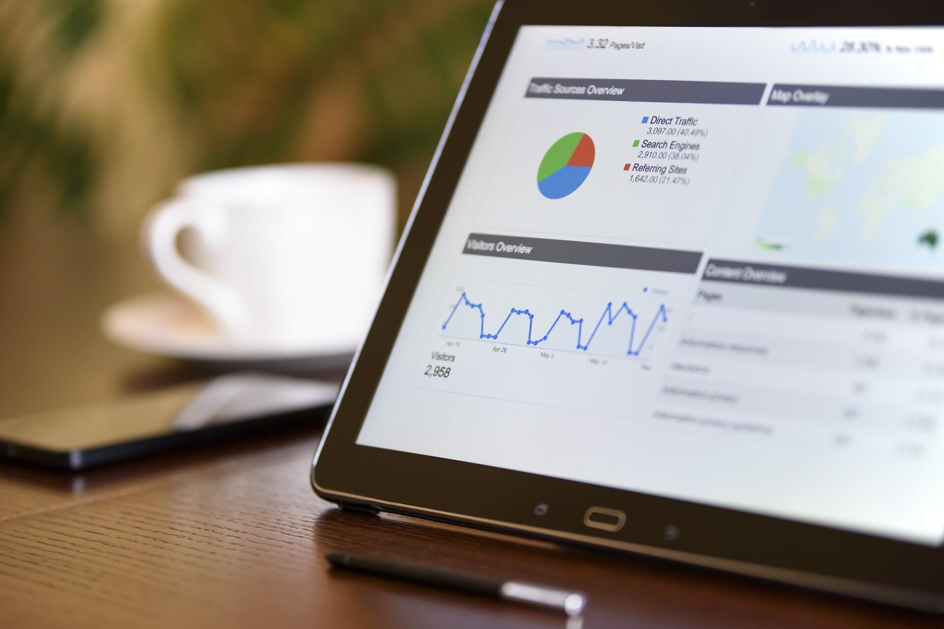 Vemos um tablet com vários gráficos em tela (imagem ilustrativa). Texto: franquia de marketing digital waybiz.
