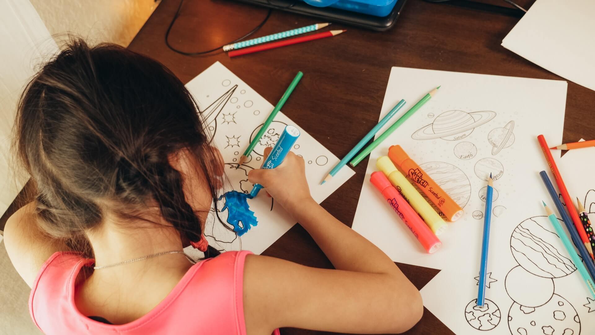 Vemos uma criança colorindo alguns desenhos impressos em papel (imagem ilustrativa). Texto: franquia de recreação infantil YouPlay.