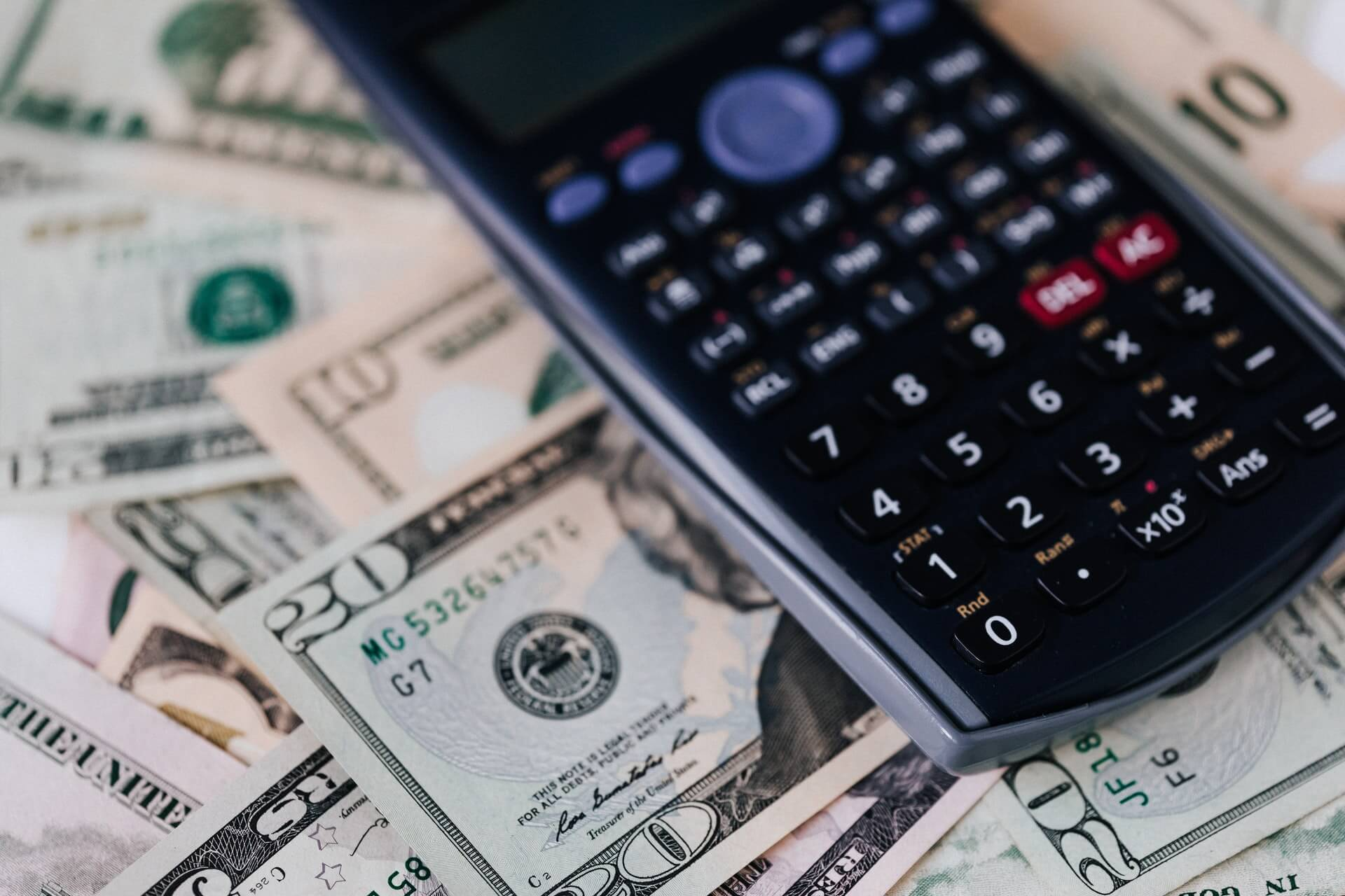 Vemos uma calculadora sobre um monte de notas de dinheiro (imagem ilustrativa). Texto: franquia de recreação infantil YouPlay.