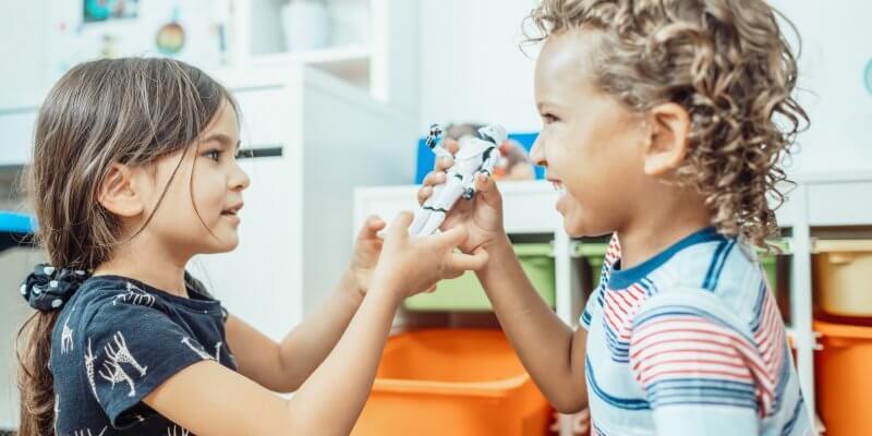 Imagem de duas crianças, uma menina e um menino, brincando e rindo. Imagem ilustrativa texto franquia de recreação infantil YouPlay.