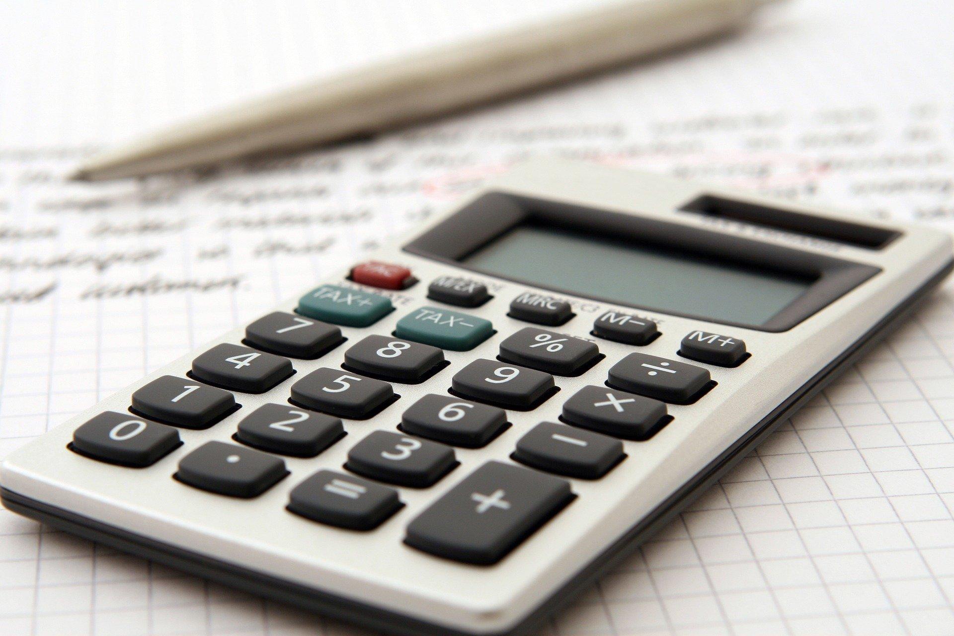 Vemos uma calculadora em cima de um papel com anotações (imagem ilustrativa). Texto: franquia de recuperação de crédito reduza veículos.