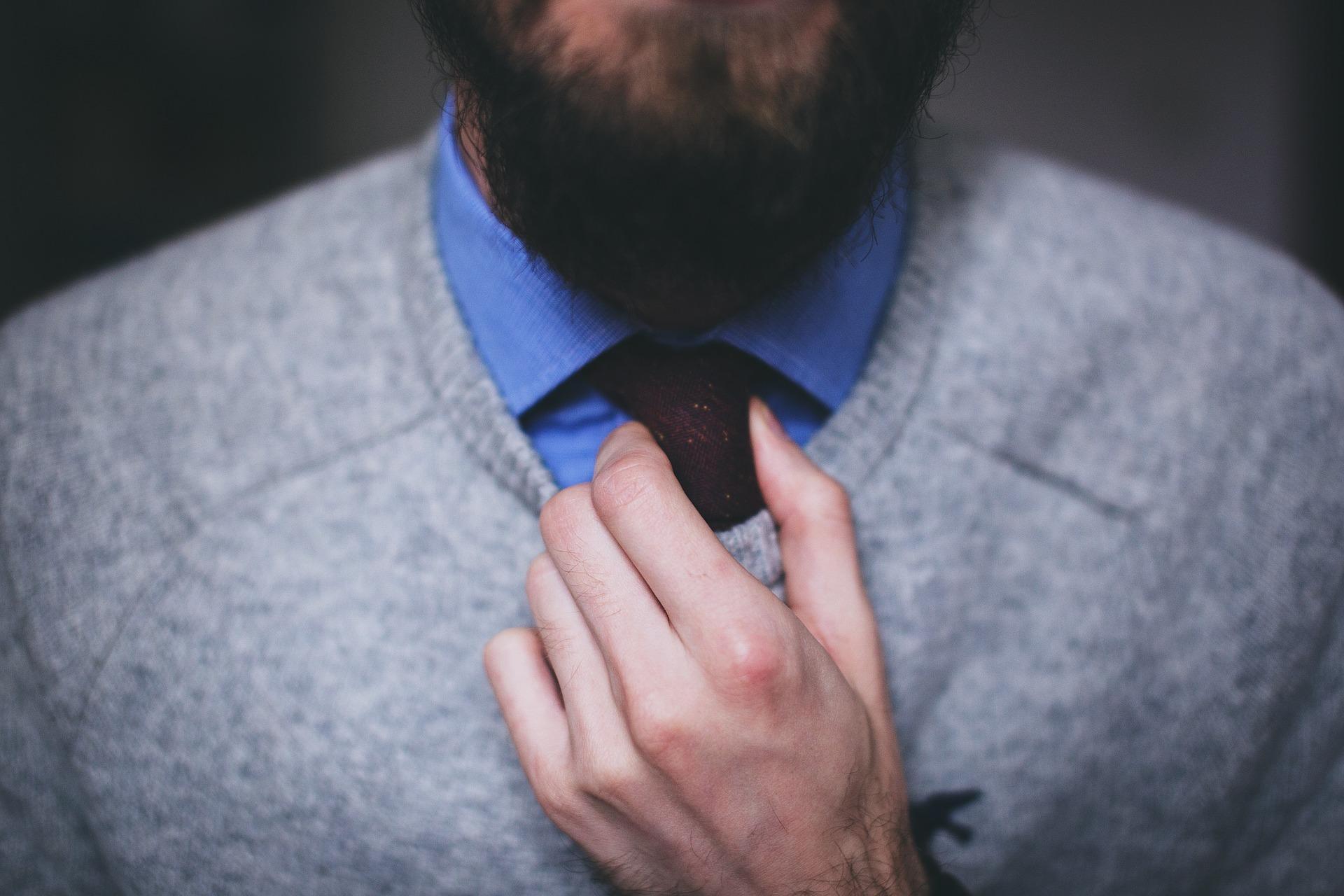 Vemos um homem de suéter ajeitando a gravata (imagem ilustrativa).