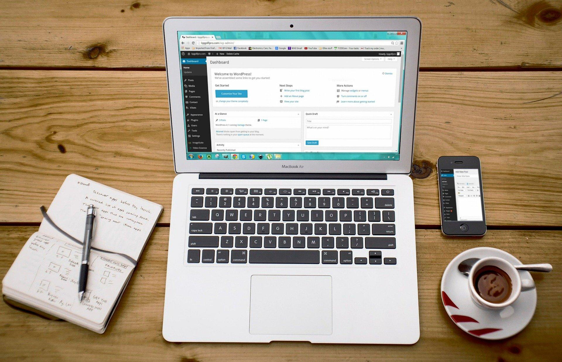 Vemos um computador em uma mesa de madeira ,com xícara de café, celular e caderno ao redor (imagem ilustrativa). Texto: franquia home office primeiro mundo.