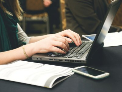 Pessoa usando computador com caderno ao lado. Imagem ilustrativa para texto franquia home office primeiro mundo.