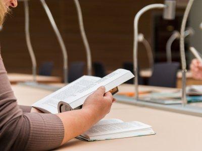 Foto de uma pessoa estudando com livro. Imagem ilustrativa para texto franquia qcarreira.