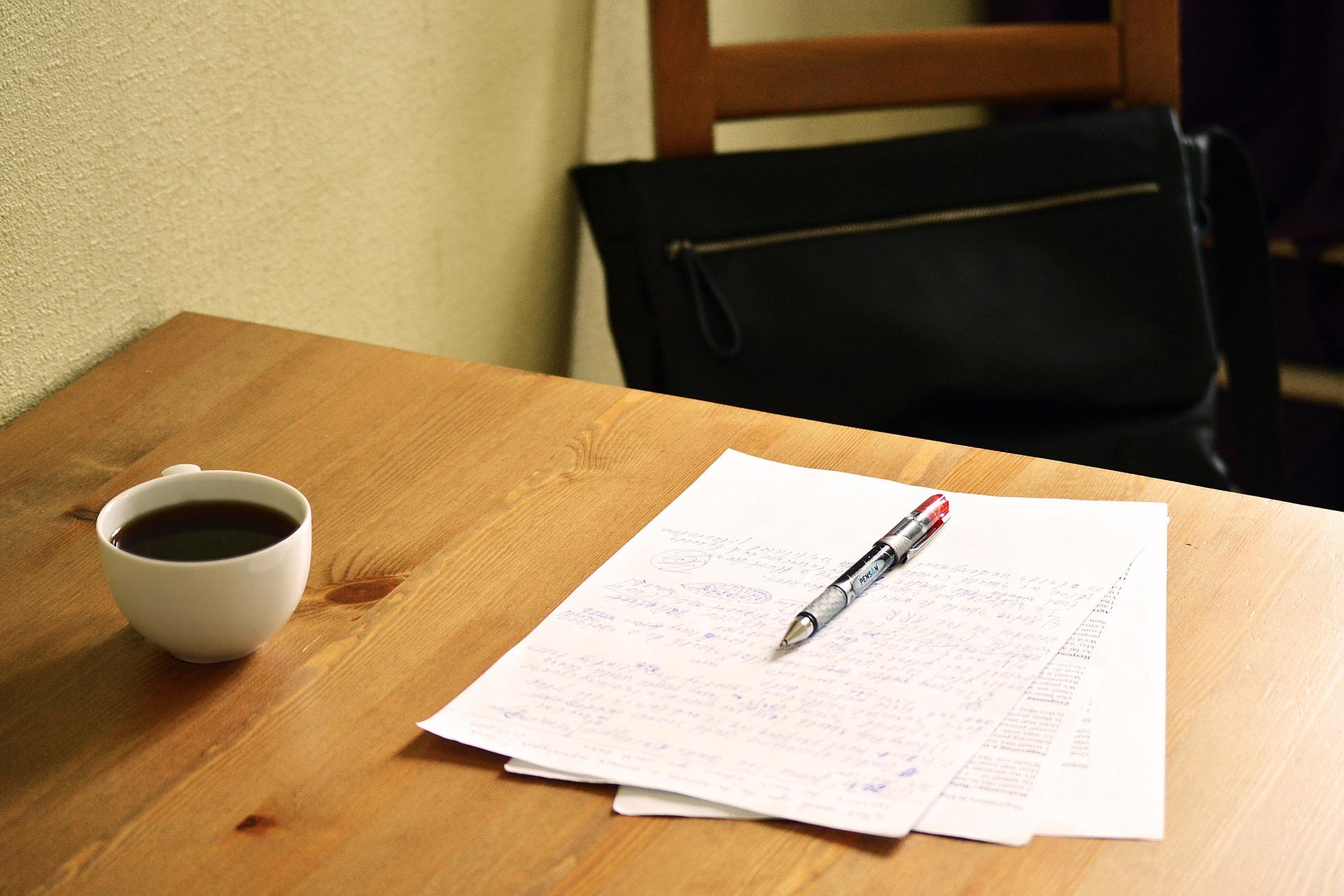 Vemos, sobre uma mesa, uma xícara de café, papéis e caneta (imagem ilustrativa). Texto: franquia qcarreira.