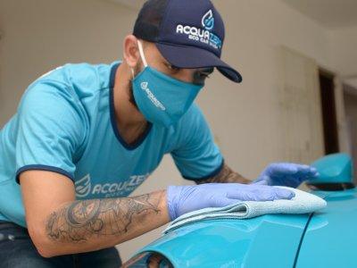 Funcionário Acquazero de uniforme limpando um veículo. Imagem ilustrativa para texto franquia de limpeza delivery.
