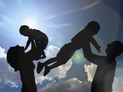 Foto de pais segurando filhos no ar. Imagem ilustrativa para texto franquia de seguro de vida.