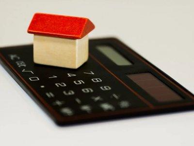 Foto da miniatura de uma casa perto de uma calculadora. Imagem ilustrativa para texto franquia de seguro residencial.