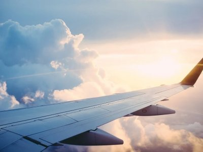 Foto da asa de um avião no céu. Imagem ilustrativa para texto franquia de turismo.